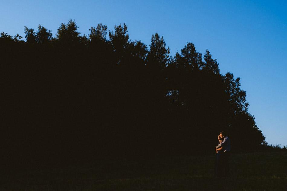 przytulająca się para w świetle wschodzącego słońca na czarnym tle lasu