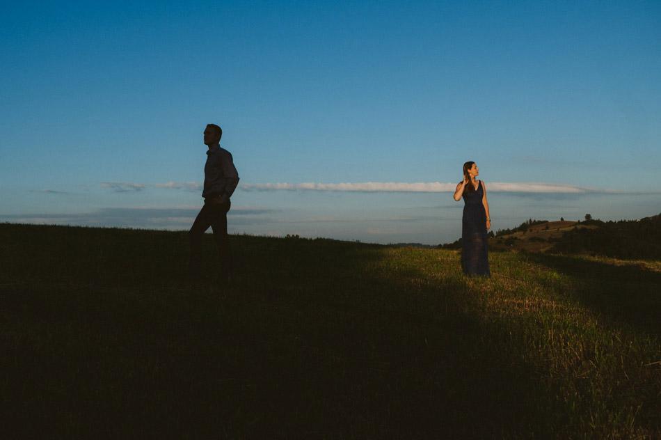 sylwetka chłopaka stojącego w cieniu oraz dziewczyny stojącej w świetle wschodzącego słońca